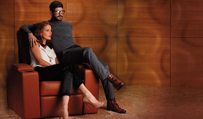 Couple sitting on single cinema chair with orange background