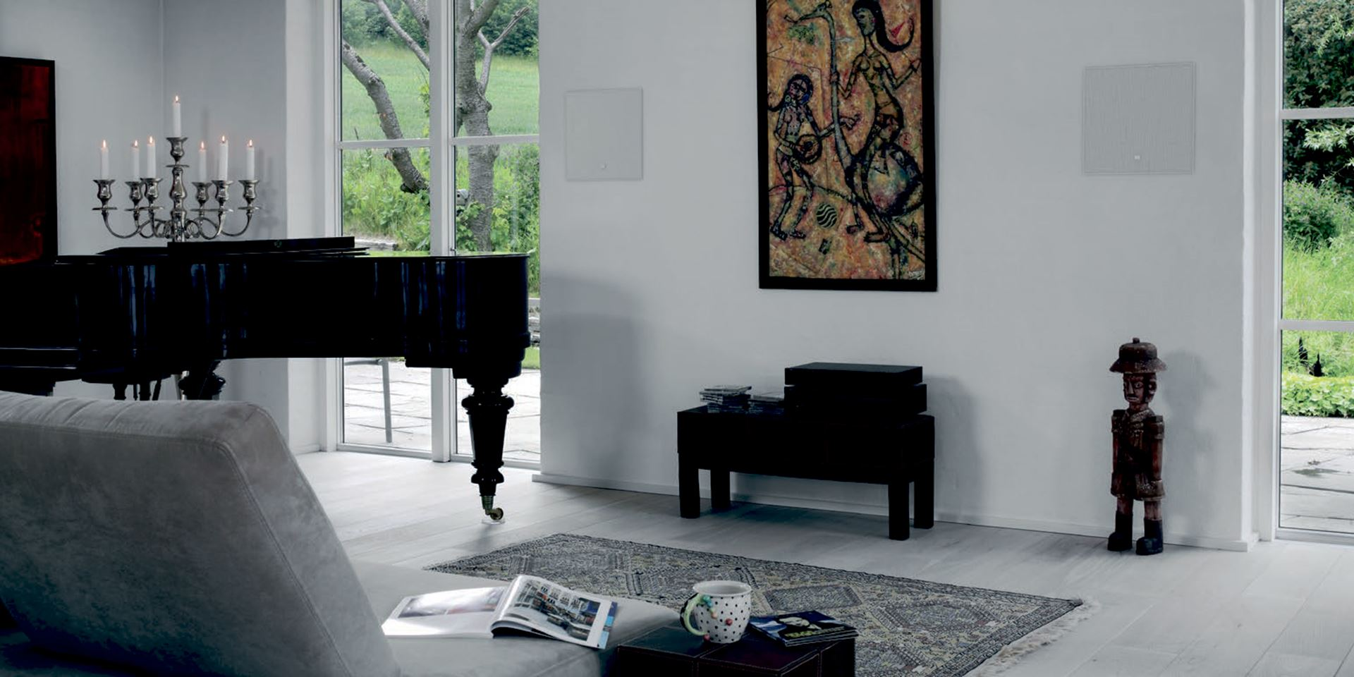 Two in-wall speakers in wall with a white grille next to a black piano in a modern living space