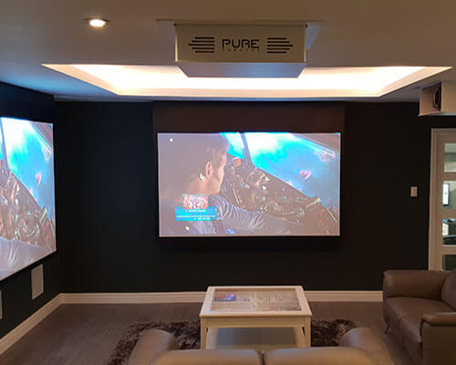 Home cinema demo room showing projector screens and two projector lifts with sofas and coffee table