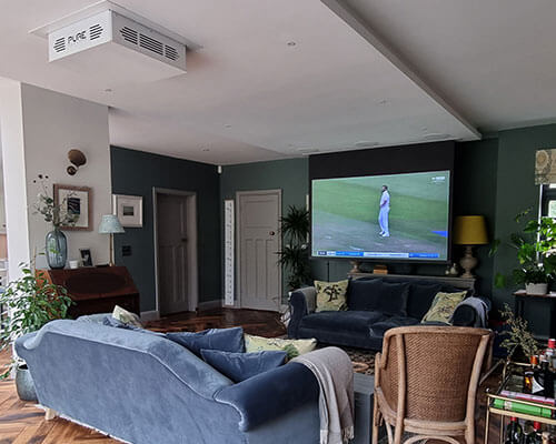Living room with blue sofa showing projector and screen showing sports