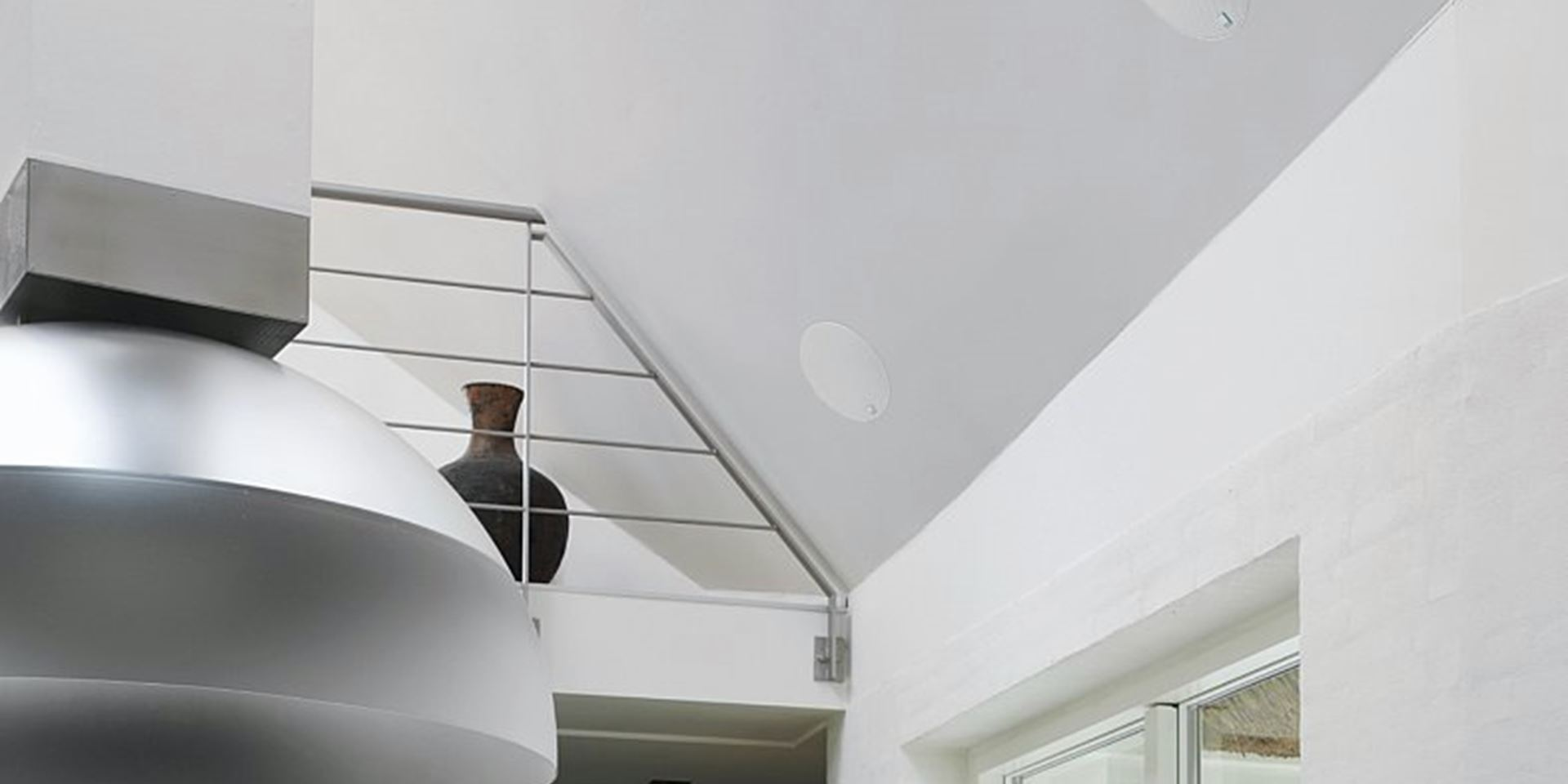 In Ceiling speaker on a white wall ledge in a house