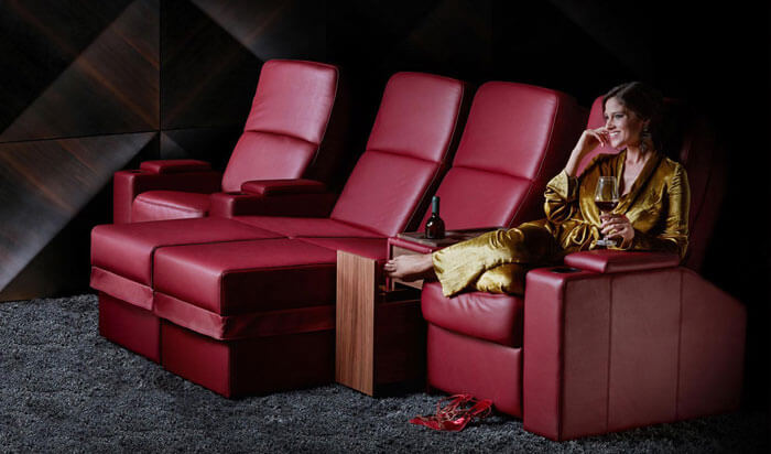 Set of red cinema chairs and loungers with women sitting with feet up